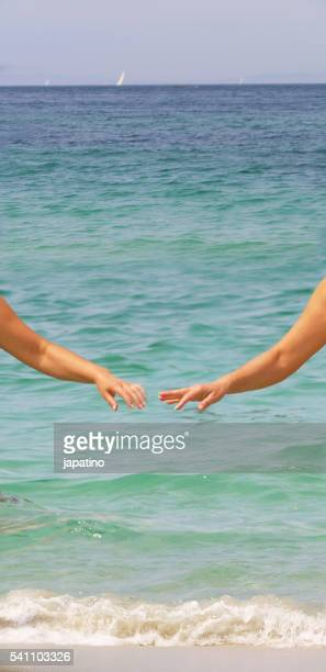 Two beautiful women arms out of the water on a beach