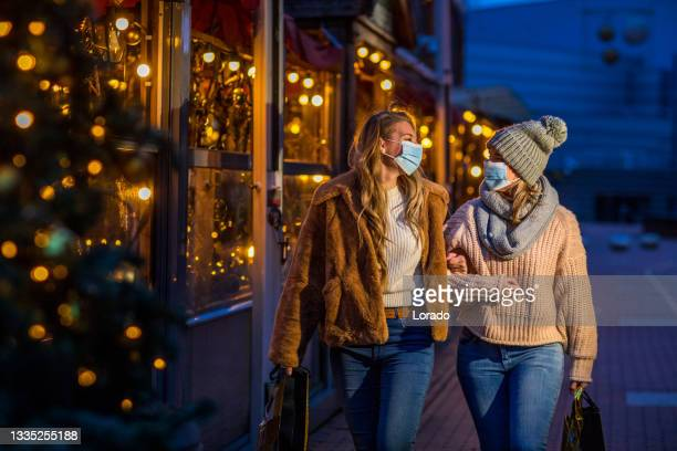 two beautiful women at winter shopping during the corona virus pandemic - north holland stock pictures, royalty-free photos & images