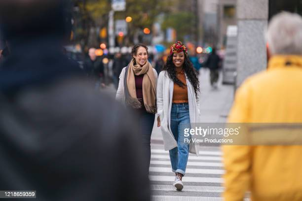 two beautiful women crossing busy city street - busy sidewalk stock pictures, royalty-free photos & images