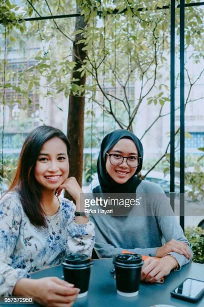 two beautiful women having break after meeting - rifka hayati stock pictures, royalty-free photos & images