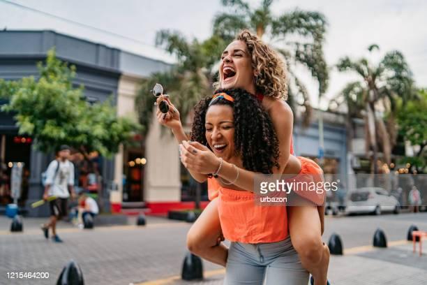 due belle donne che si divertono - portare a cavalluccio foto e immagini stock