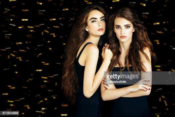 two beautiful women - gold dress stock pictures, royalty-free photos & images