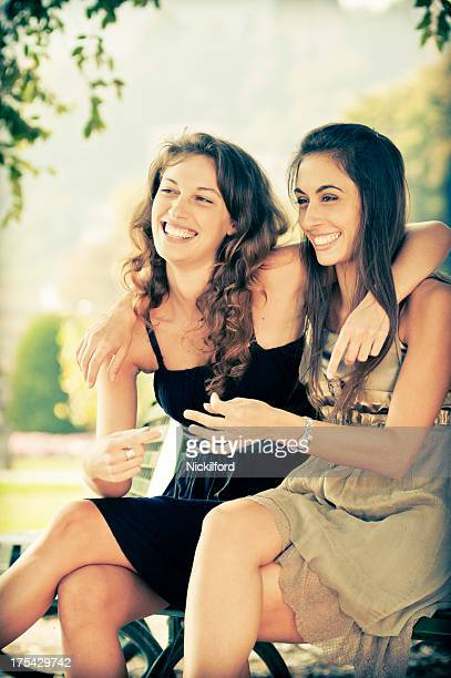 Two beautiful women sitting on a park bench