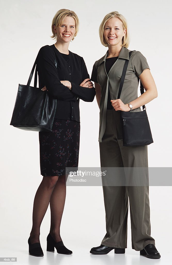 two beautiful  young caucasian women with shoulder length blond hair dressed in businees attire and purses standing together smiling into the camera : Foto de stock