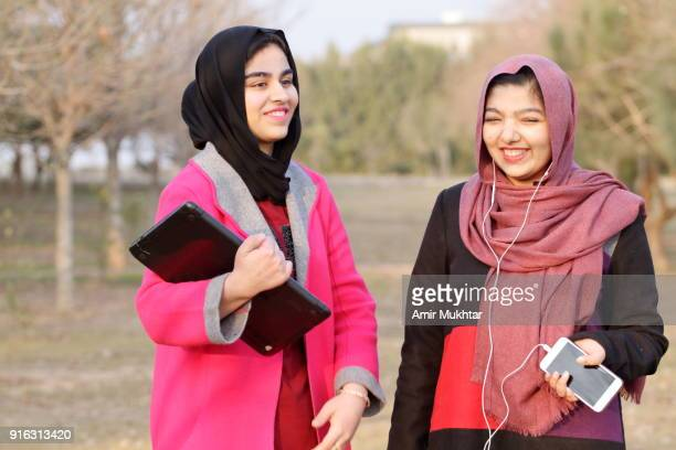 two beautiful young girls in hijab (head scarf) walking and talking in the park at day time while holding a laptop and cell phone. - pakistan girl stock photos and pictures