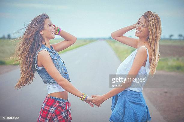 Two beautiful, young smiling women holding hands and sharing moment