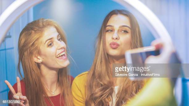 Two beautiful young woman are taking a selfie in front of the mirror