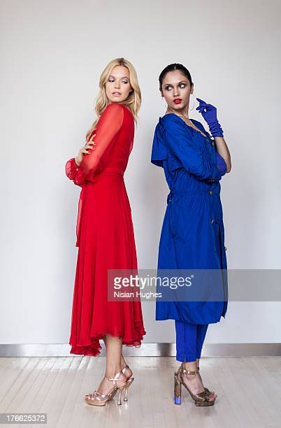 two beautiful young woman standing back to back - rivaliteit stockfoto's en -beelden