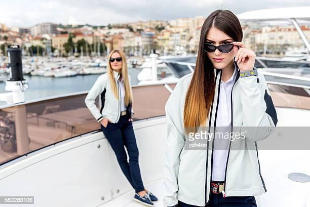two beautiful young women posing on yacht - lichaamshouding stockfoto's en -beelden