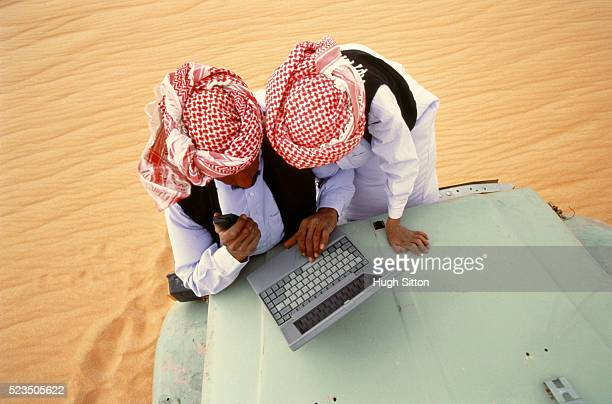 Two bedouins using laptop and mobile phone, Sahara desert, Egypt, Africa