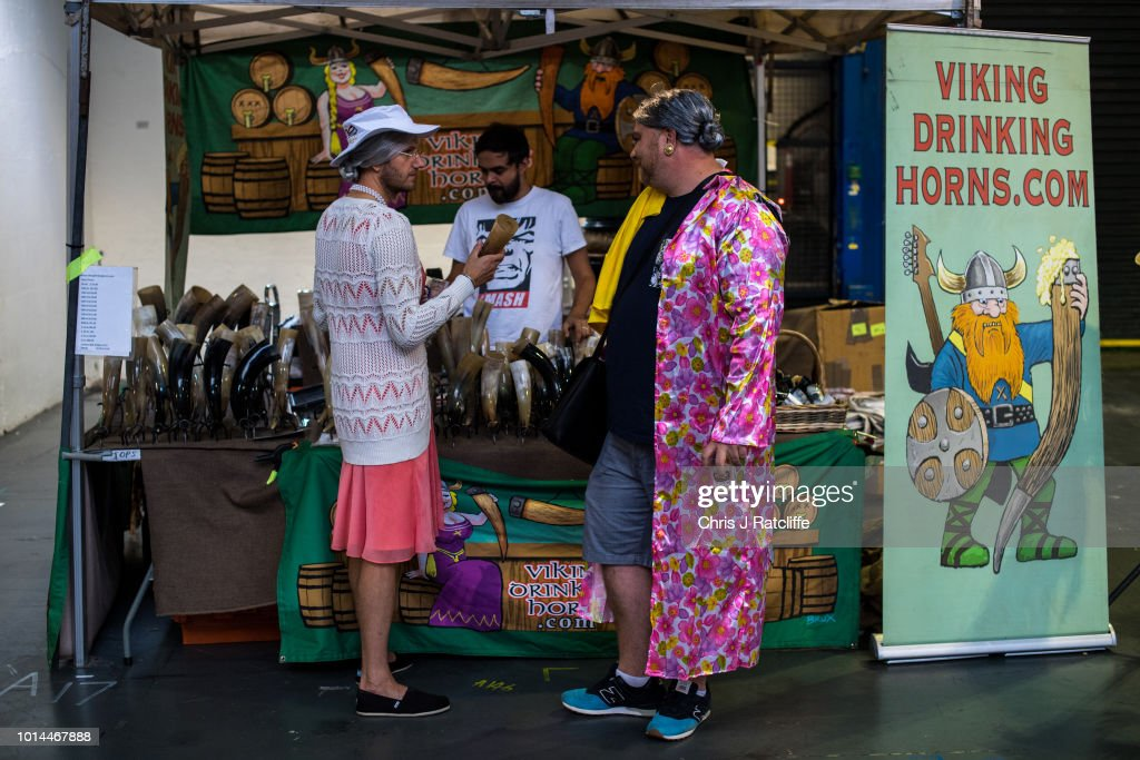 Two beer enthusiasts in women's dress look at drinking horns for sale during the Great British Beer Festival at Olympia Exhibition Centre on August 10, 2018 in London, England. The five day festival showcases over 900 real ales and craft beer and is organised by Campaign for Real Ale group CAMRA.