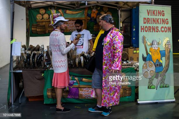 Two beer enthusiasts in women's dress look at drinking horns for sale during the Great British Beer Festival at Olympia Exhibition Centre on August...