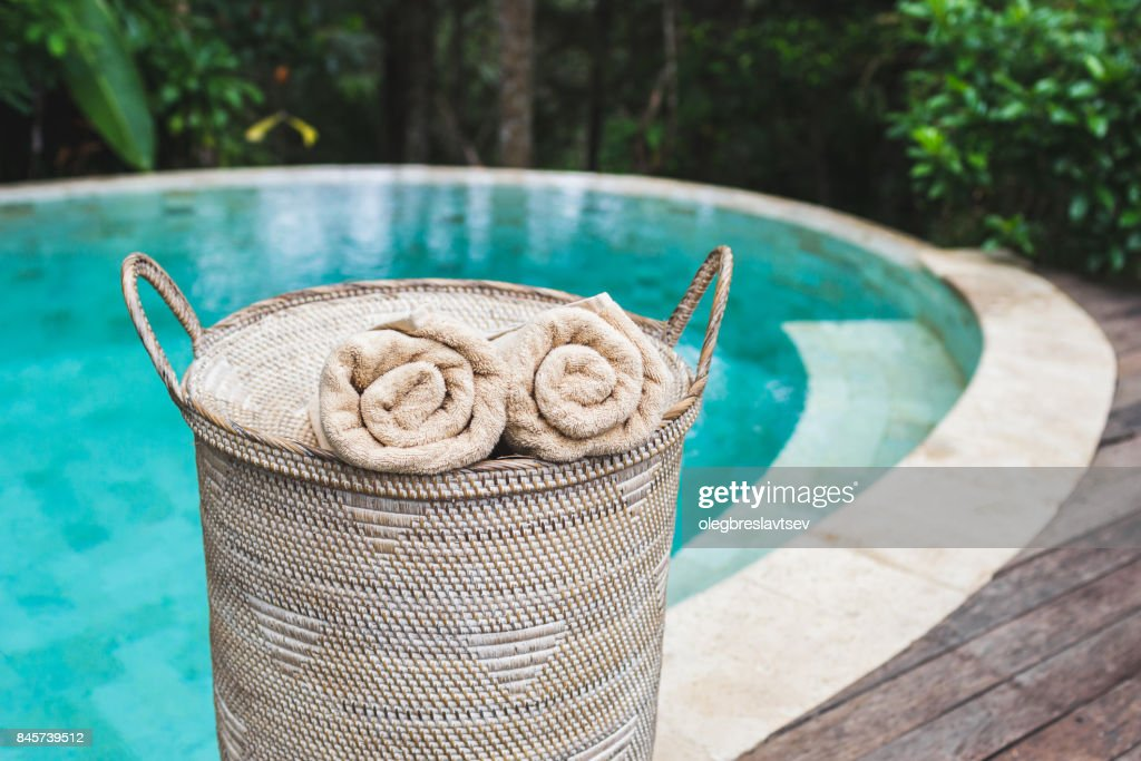 Two Beige Rolled Towels In Wicker Basket Near Private Pool With Turquoise Clear Water Stock