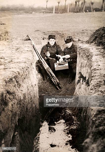 Two Belgian soldiers having a Christmas meal in a dry corner of a flooded trench on the Western Front during World War One circa December 1915