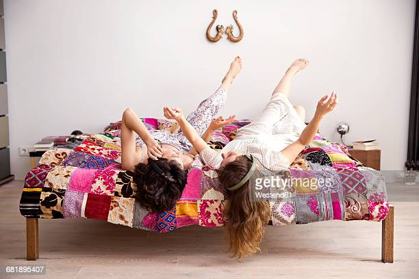 two best friends lying on bed with legs in the air listening music with headphones - patchwork stock pictures, royalty-free photos & images