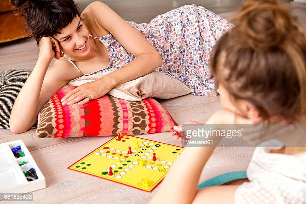 Two best friends lying on the floor at home playing ludo