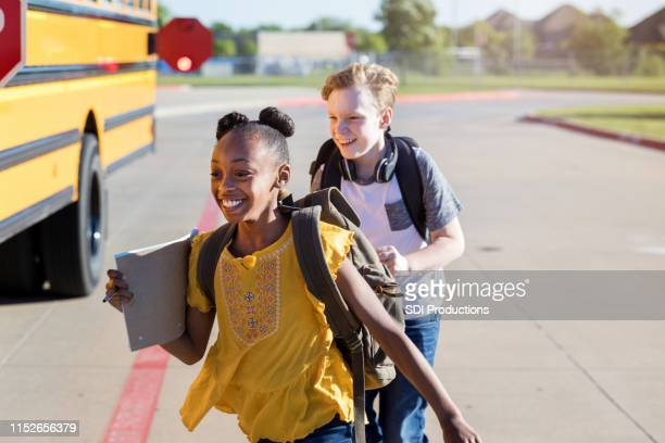 two best friends race to the school bus - field trip stock pictures, royalty-free photos & images