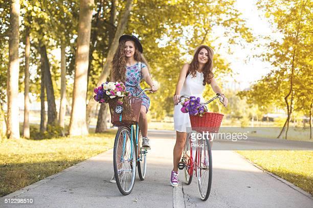 Two best friends riding bicycles in a park