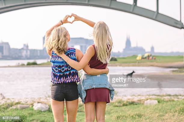Two best friends shaping heart with their hands at riverbank