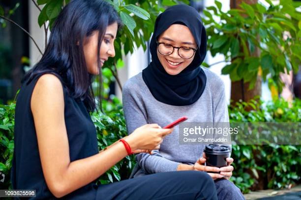 Two best friends sharing good laugh while looking at smart phone
