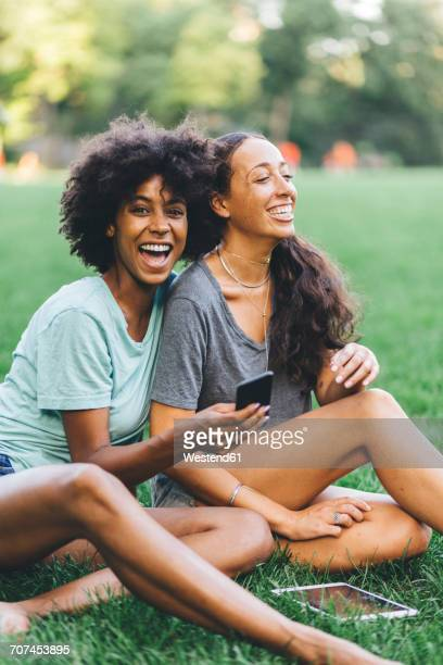 Two best friends sitting on a meadow of a park having fun with mini tablet