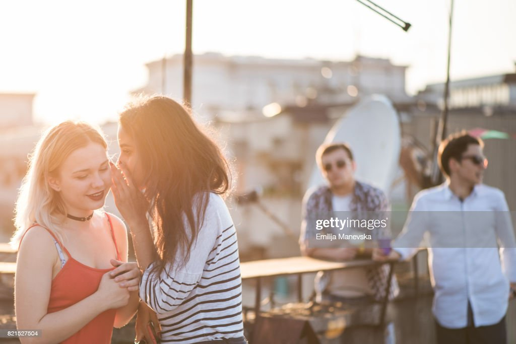 Two best friends standing at the roof top party and gossiping : Stock Photo