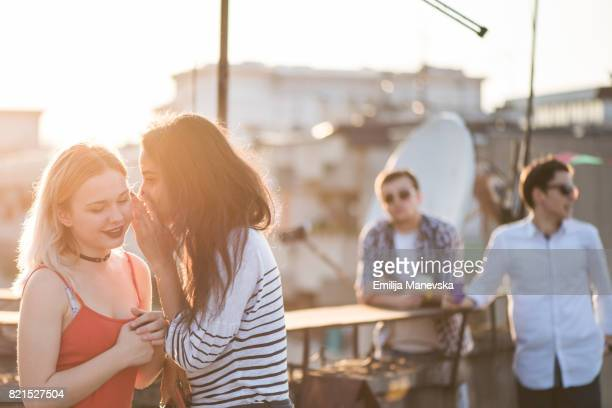 Two best friends standing at the roof top party and gossiping