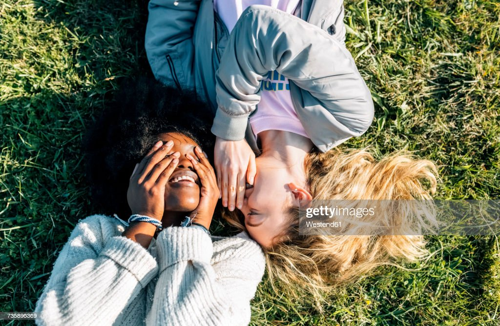 Two best friends telling secrets lying in the grass : Stock Photo