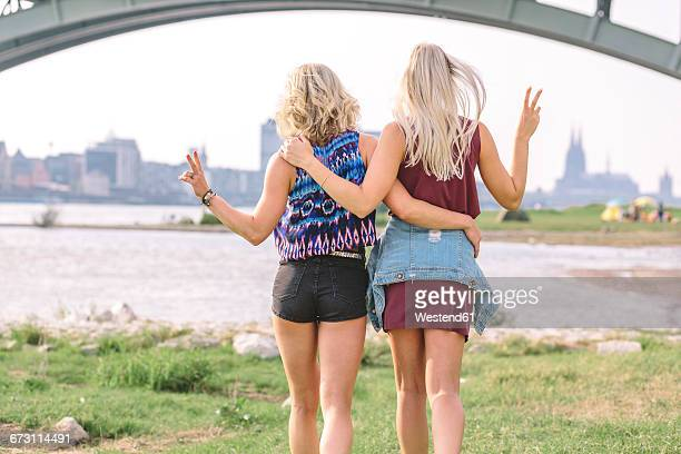 Two best friends walking arm in arm at riverbank
