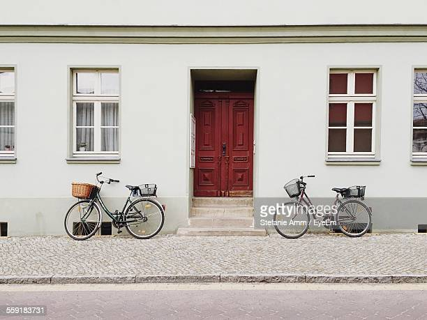 Two Bicycles Leaning Against House Wall