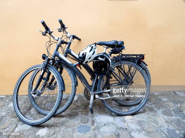 two bicycles of mountain with in hung hull supported on a wall in the city - sports helmet stock pictures, royalty-free photos & images