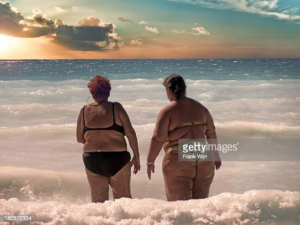 two big ladies go swimming in the sea at sunset - swimwear stock photos and pictures
