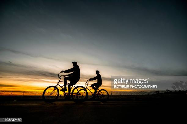 two bike rider silhouettes riding at sunset on santa monica beach, los angeles california - golden hour stock pictures, royalty-free photos & images