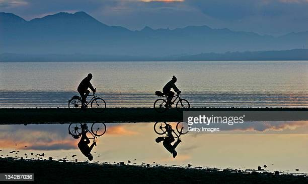 Two biker cycle in front of the Chiemsee lake and Bavarian mountains on November 29 2011 near Seebruck Germany A drought in Germany in November has...