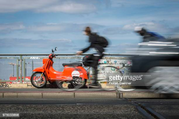 Two bikers and a car are pictured in front of an 'emmy' eScooter on June 14 2018 in Berlin Germany Emmy is a sharingbased provider of electro...