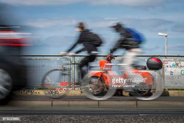 Two bikers and a car are pictured in front of an 'emmy' eScooter on June 14, 2018 in Berlin, Germany. Emmy is a sharing-based provider of electro...
