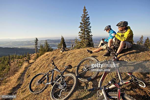 Two bikers resting on trail in Alps, Garmisch-Partenkirchen, Germany