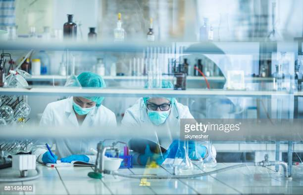 Two biotechnologists examining data for medical research in the laboratory.