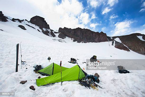 Two bivy sacks and skis indicate a campsite in the middle of snowfield..