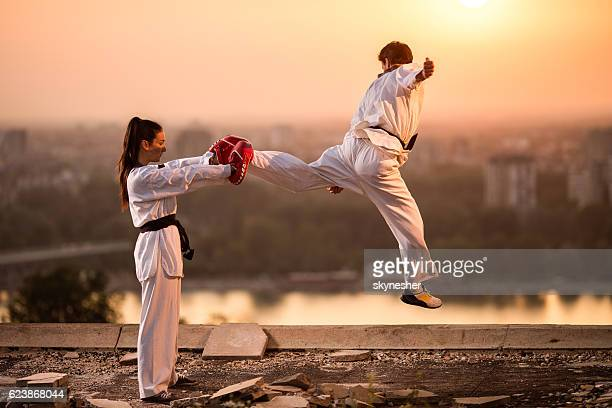 Two black belt sparring partners exercising at sunset.