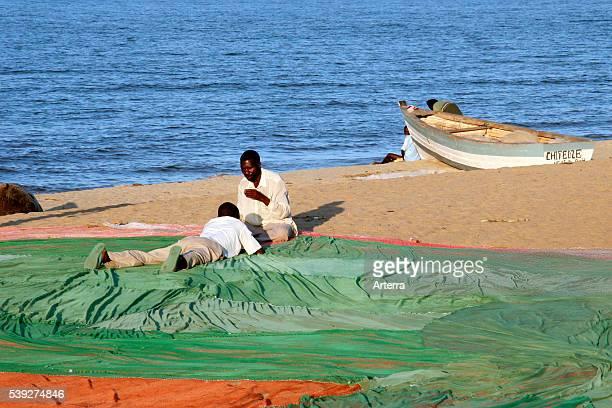 Two black fishermen mending sail of fishing boat on the beach along Lake Malawi Malawi Africa
