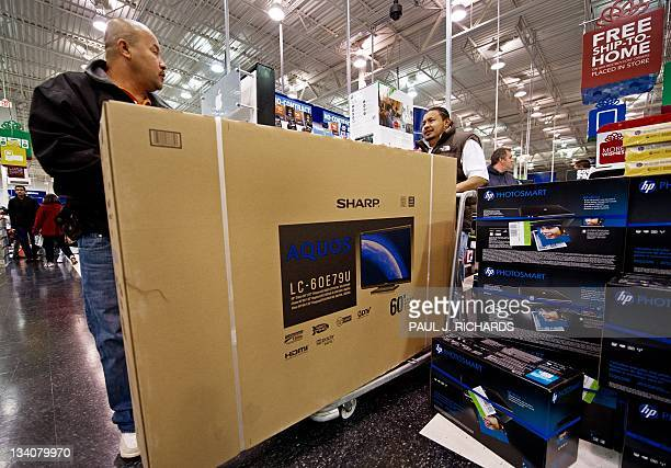 Two Black Friday customers wheel away their Aquos/Sharp 60 LCD TV to the checkout counter at the Fair Lakes Best Buy store in Fairfax Virginia on...