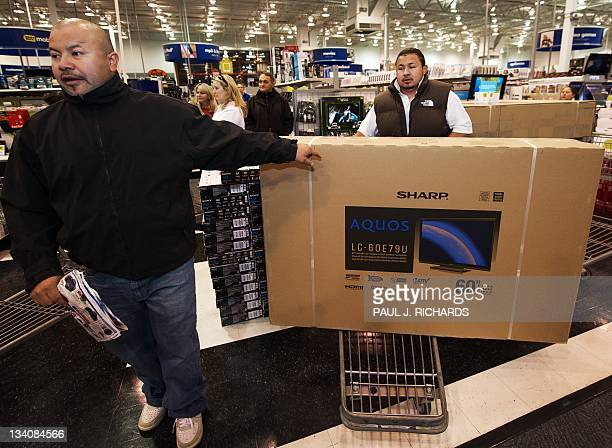 Two Black Friday shoppers take their Aquos/Sharp 60 LCD TV to the cashier on Black Friday on November 25 2011 at the Fair Lakes Best Buy store in...