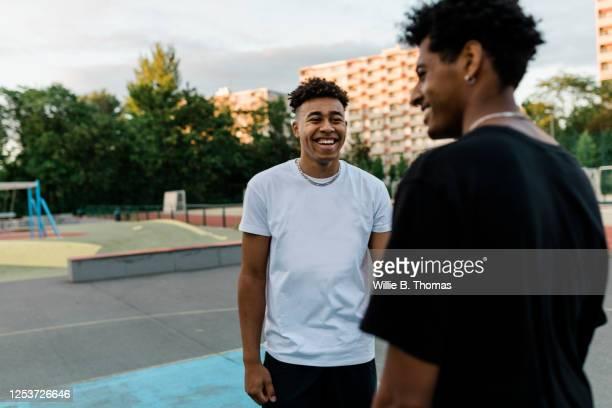 two black friends talking on basketball court - trefferversuch stock-fotos und bilder