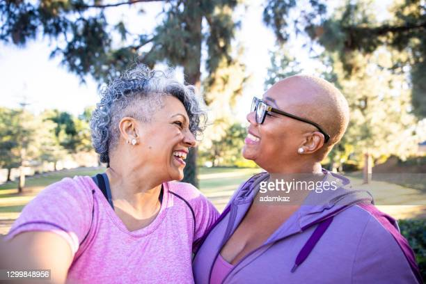 two black lady friends taking selfies - adamkaz stock pictures, royalty-free photos & images