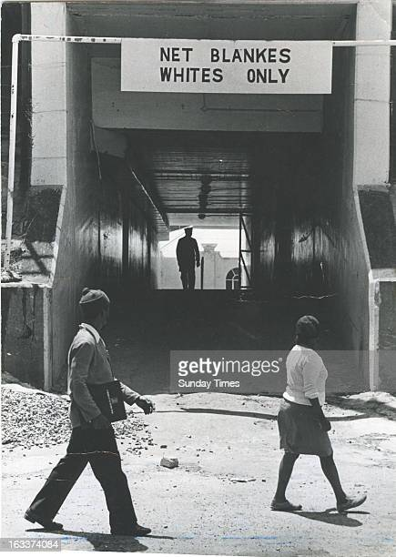 Two black people pass a 'Net Blankes Whites Only' sign on October 7 1977 in South Africa
