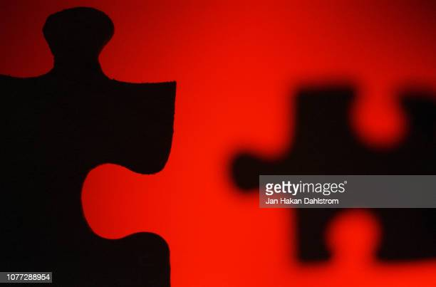 two black puzzle pieces on red background - things that go together stock pictures, royalty-free photos & images