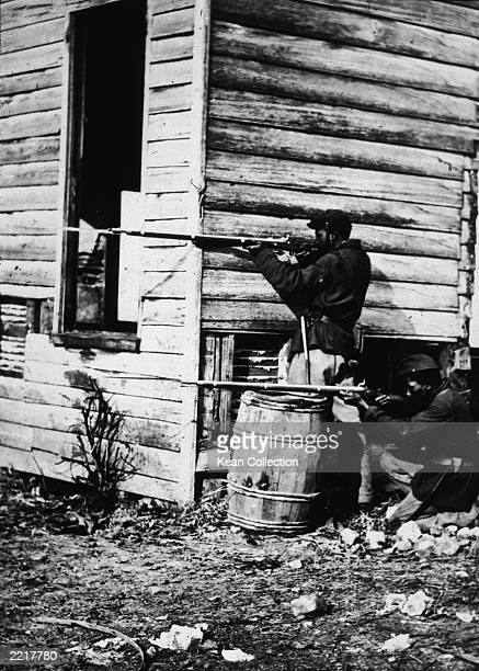 Two Black soldiers in the Union Army aim their rifles beside a corner of a builidng in 'Picket Post' a Mathew Brady photograph from the American...