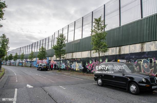 two black taxis and people in front of  the belfast wall separating catholics from protestants during day of autumn - belfast stock pictures, royalty-free photos & images