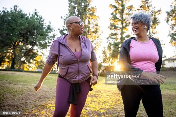 twee zwarte vrouw die door een grasgebied loopt - wandelen lichaamsbeweging stockfoto's en -beelden